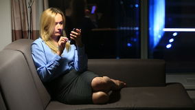 Business woman, blonde browsing the internet using the phone. In real time. Panoramic window and a night city on a stock footage