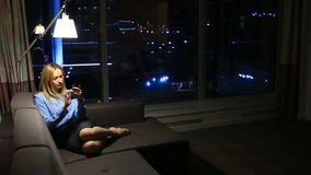 Business woman, blonde browsing the internet using the phone. In real time. Panoramic window and a night city on a stock video