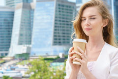 Business woman blonde holding coffee outdoors on city background stock photo