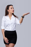 Business woman blowing on palm. Beautiful business woman blowing on palm, looking far away upwards, over grey background Stock Photo