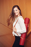 Business woman with blue eyes in white blouse shirt and black pants holding, carrying yoga mat in office Stock Photo