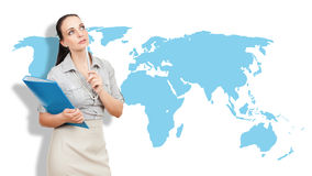Business woman with a blue folder. A business woman with a blue folder and a pencil in front of an earth map royalty free stock images