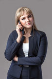 Business woman in blue suit talking on the phone. Gray background stock images