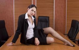 Business woman on boardroom table. Brunette business woman with black suit on boardroom table Royalty Free Stock Photos