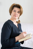 Business woman with book and pen in hand Stock Photo