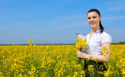 Business woman with bouquet and clipboard relaxing in flower field outdoor. Young girl in yellow rapeseed field. Beautiful spring Stock Photos
