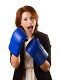 Business woman boxing. Businesswoman in suit punching with red boxing gloves isolated on white background Stock Image