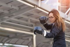 Business woman boxing gloves - business competition concept with. Businesswoman punching and hitting standing Royalty Free Stock Image