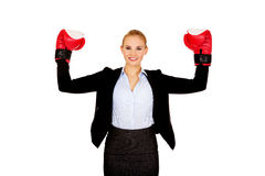 Business woman in boxing gloves standing in victory pose Royalty Free Stock Image