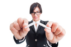 Business woman breaking a cigarette in half Royalty Free Stock Photos