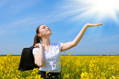 Business woman with briefcase relaxing in flower field outdoor under sun. Young girl in yellow rapeseed field. Beautiful spring la. Ndscape, bright sunny day stock images