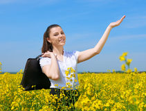Business woman with briefcase relaxing in flower field outdoor under sun. Young girl in yellow rapeseed field. Beautiful spring la Stock Photo
