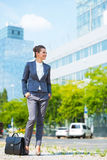 Business woman with briefcase standing in modern office district Royalty Free Stock Images