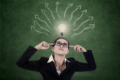 Business woman with bright light and mind map. Businesswoman is searching for ideas with bright light bulb and arrows to represent mind map stock photo