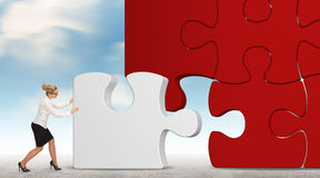 Business woman building a puzzle on a sky background Royalty Free Stock Photography