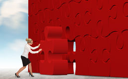 Business woman building a puzzle on a sky background Royalty Free Stock Photo