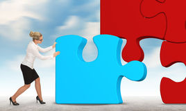 Business woman building a puzzle on a sky background. Stock Image