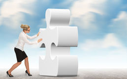 Business woman building a puzzle on a sky background Royalty Free Stock Image