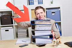 Business woman with burnout. Pointing arrow to files in her office Royalty Free Stock Photos