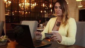 Business woman in business attire commits online purchase using a credit card having a good mood. Beautiful business woman in a bright jacket with long blond stock footage