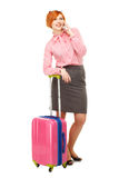 Business woman in business trip with a suitcase on wheels speaki Stock Image