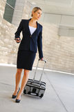 Business woman in business trip walking with wheel bag and speak Stock Image