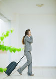 Business woman in business trip with wheel bag Stock Photo