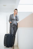 Business woman in business trip with wheel bag Stock Photos