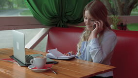 Business woman in a cafe talking on cell phone writing in dairy stock video footage