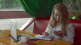 Business woman in a cafe working with smartphone laptop and notebook stock video footage