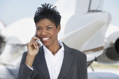 Business Woman On Call At Airport Stock Photo