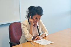 Business woman call to inquire more details about document. And thinking Royalty Free Stock Photo