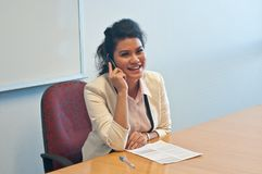 Business woman call to inquire more details and talk. Over phone and smile Royalty Free Stock Images