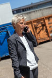 Business woman is calling in front of containers Royalty Free Stock Image