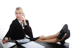 Business woman calling by phone. Portrait young blonde business woman calling by phone and put legs on a Stock Photography