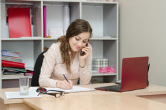 Business woman calling by phone and does records Royalty Free Stock Image