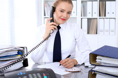 Business woman calls by phone making report, calculating or checking balance. Stock Photo