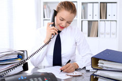 Business woman calls by phone making report, calculating or checking balance. Stock Image
