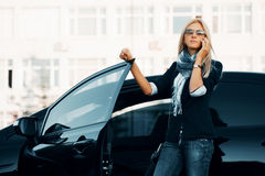 Fashion business woman in sunglasses calling on phone next to car Stock Photography