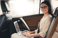 Business woman in car. Beautiful business woman in eyeglasses is using a laptop and smiling while sitting on back seat in the car Royalty Free Stock Image