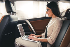 Business woman in car. Beautiful business woman in eyeglasses is using a laptop and smiling while sitting on back seat in the car Stock Images