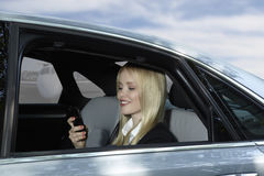 Business Woman in car with mobile phone at airport Royalty Free Stock Image