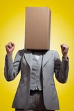Business woman with a cardboard box head. On a yellow background Royalty Free Stock Photos