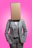 Business woman with a cardboard box head. On a magenta background Royalty Free Stock Photos