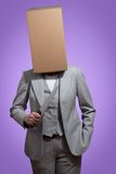 Business woman with a cardboard box head holding a knife Stock Image