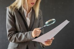 Woman carefully reading business contract with magnifying glass. Business woman carefully reading business contract with magnifying glass stock images