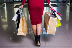 Business woman carrying shopping bags while walking  mall. Day shopping. Closeup beautiful legs of  business woman carrying shopping bags while walking along the Royalty Free Stock Photo