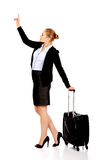 Business woman carrying a suitcase and looking up Stock Images