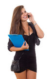 Business woman carying folder and purse talking on the phone Royalty Free Stock Image