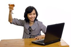 Business Woman Celebrating Her Success with Wine. Beautiful asian business woman celebrating her success with wine in front of her computer Royalty Free Stock Photo
